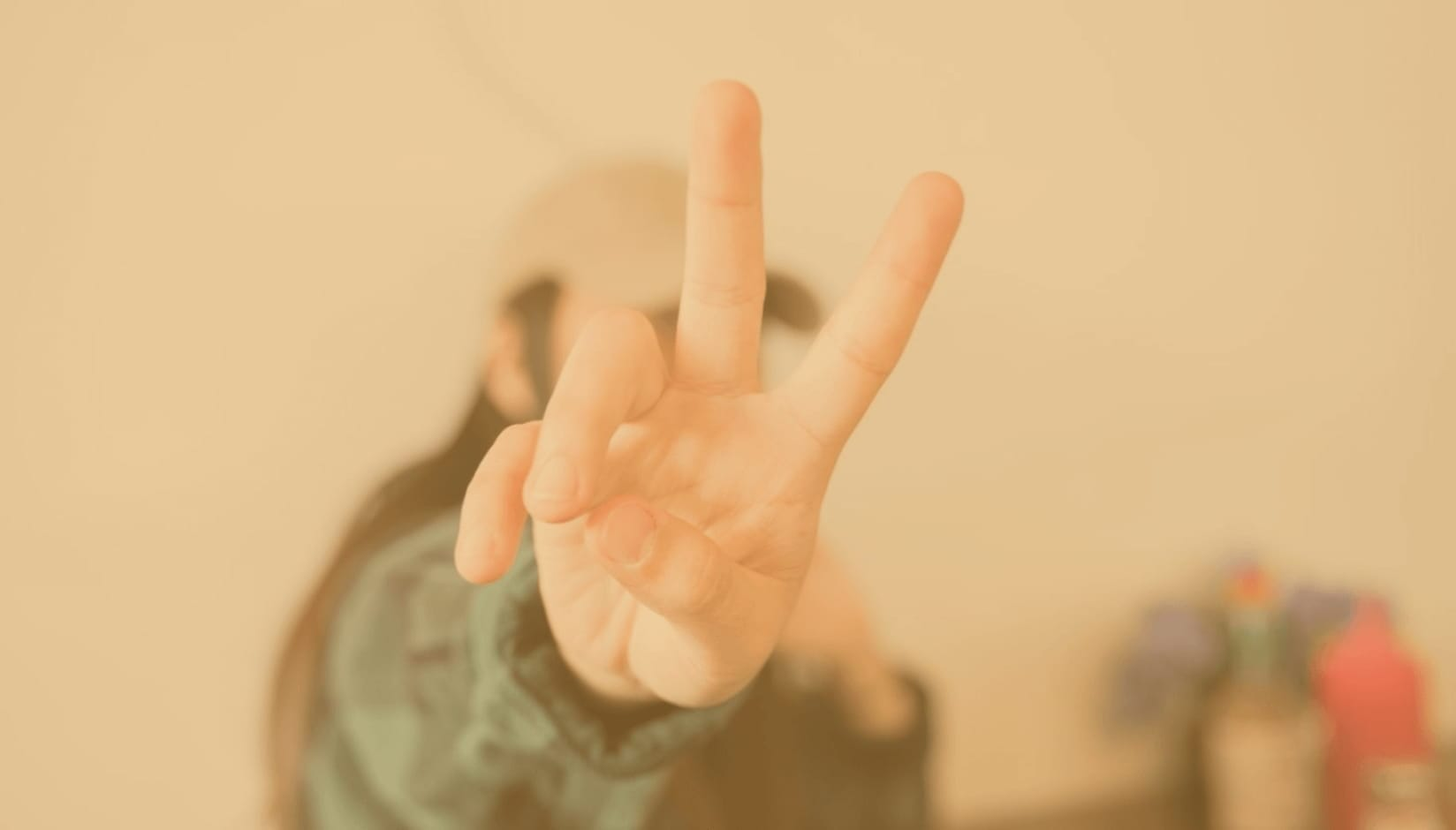 girl showing v sign with her fingers
